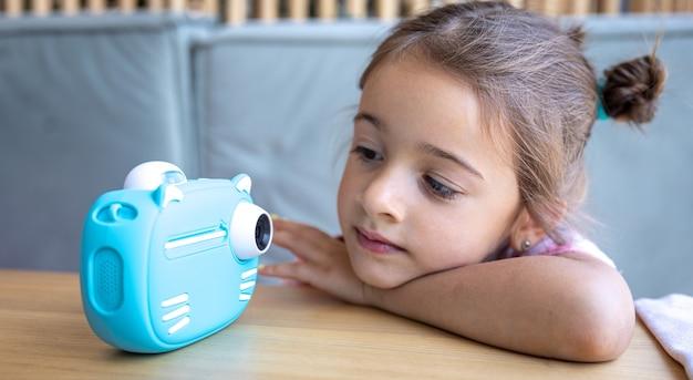 귀여운 소녀가 즉석 사진 인화를 위해 아이들의 파란색 장난감 카메라를 쳐다보고 있습니다.