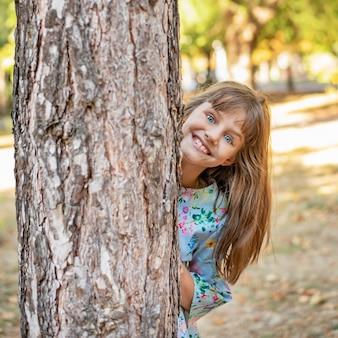Милая маленькая девочка с улыбкой смотрит из-за дерева в парке.