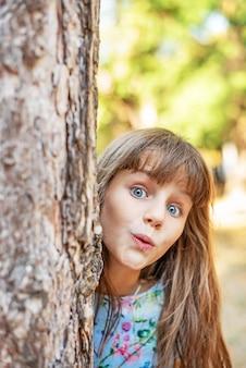 귀여운 소녀는 공원에서 나무 뒤에서 밖으로 보인다.