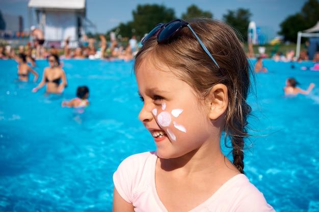 彼女の頬に太陽の形をした日焼け止めとプールの横にあるかわいい女の子