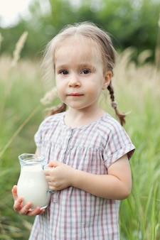 밀밭에 귀여운 땋은 머리를 한 2~3년 된 귀여운 소녀가 우유 한 병과 미소를 지으며 카메라를 쳐다봅니다. 자연 산책