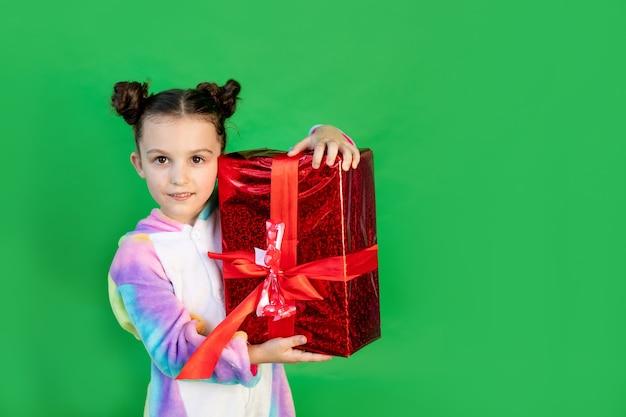 明るいスーツで孤立した緑の背景にかわいい女の子。テキストのためのスペース。新年とクリスマスのコンセプト