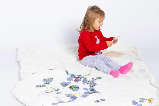 Милая маленькая девочка играет с пазлом на белом изолированном фоне, сидя на пушистом одеяле Premium Фотографии