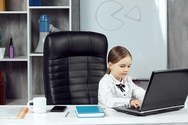 Милая маленькая девочка изображает босса, работающего за столом на ноутбуке в офисе