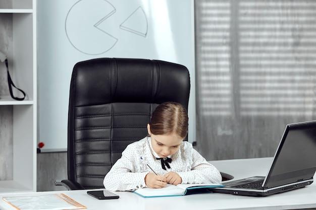 귀여운 소녀가 흰색 탁자에서 수첩에 메모를 하고 있는 에이전시 대표를 묘사합니다.