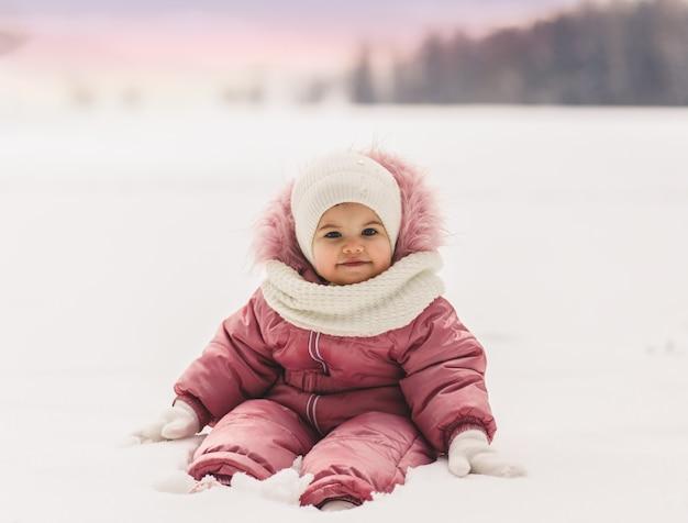 Милая маленькая девочка сидит на снегу зимой на открытом воздухе