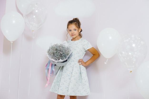Милая маленькая девочка улыбается и позирует с букетом цветов