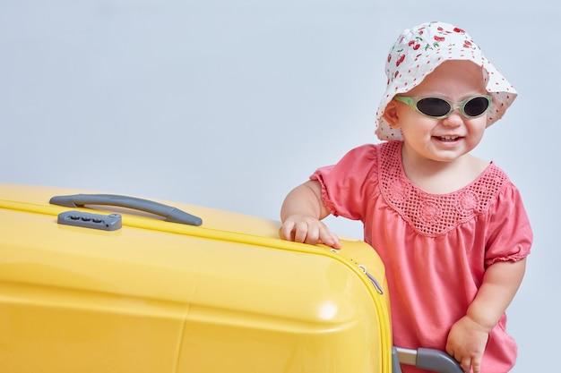 Милая маленькая девочка стоит рядом с большим желтым чемоданом. путешествуйте с детьми. место для текста.