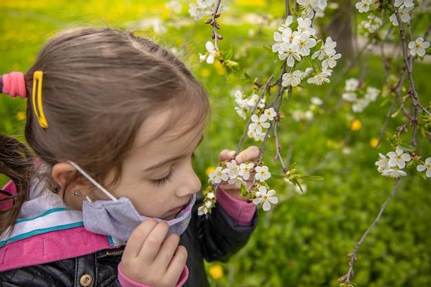 귀여운 소녀가 가면을 벗고 나무 위의 봄꽃 냄새를 맡았습니다.