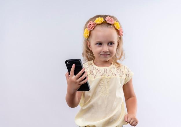 白い壁に横を見ながら携帯電話を保持している花のヘッドバンドで黄色のシャツを着ているかわいい女の子