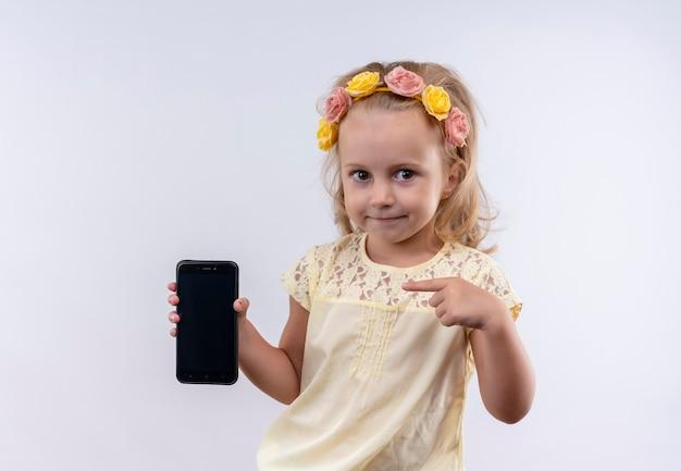 白い壁に人差し指で携帯電話の空白のスペースを指している花のヘッドバンドで黄色のシャツを着ているかわいい女の子