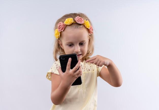 白い壁に人差し指で携帯電話を指して花のヘッドバンドで黄色のシャツを着ているかわいい女の子