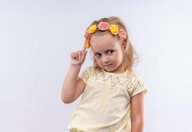 白い壁に人差し指で上向きの花のヘッドバンドで黄色のシャツを着ているかわいい女の子