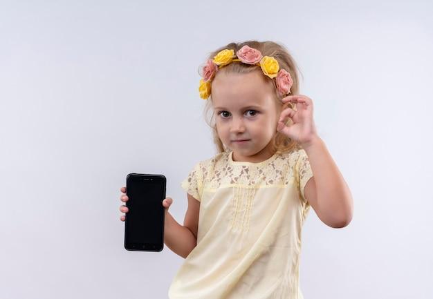 白い壁にokジェスチャーで携帯電話の空白スペースを示す花のヘッドバンドで黄色のシャツを着ているかわいい女の子