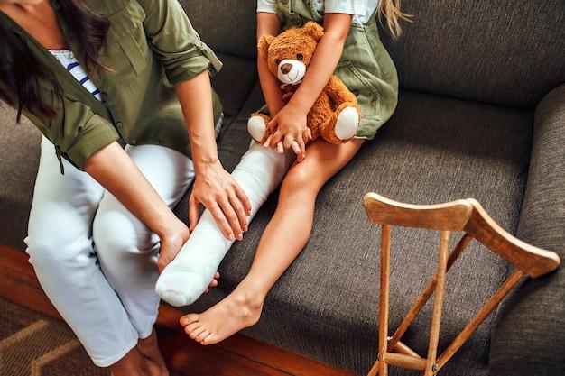 Милая маленькая девочка со сломанной ногой в гипсе сидит с мамой на диване и обнимает дома плюшевого мишку. возле дивана есть костыли для быстрой реабилитации.