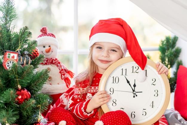 Милая маленькая девочка с часами в руках сидит на подоконнике у окна дома у елки и ждет новый год или рождество в шапке деда мороза и улыбается