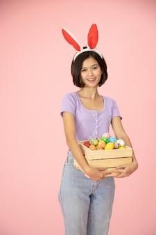 スタジオでピンク色の背景に木箱でイースターエッグを塗ったかわいい女の子。キリストの宗教の最も重要な日の一つ。イエスの復活を思い出すために Premium写真