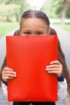 꼬리가 두 개인 귀여운 소녀가 서류가 든 폴더를 손에 들고 있습니다. 공원에서 산책, 학교로 돌아갑니다.