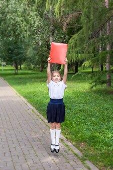 꼬리가 두 개인 귀여운 소녀가 서류가 든 폴더를 손에 들고 있습니다. 공원에서 산책, 학교로 돌아가기