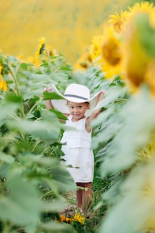 ひまわり畑でかわいい笑顔の女の子。帽子の子。子供の頃のコンセプト。ひまわり畑で日当たりの良い夏の日。セレクティブフォーカス