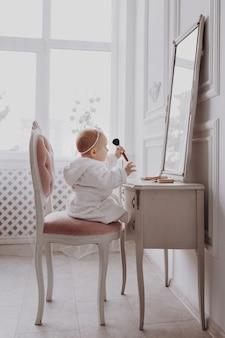 かわいい小さな女性が化粧ブラシを持って、家で楽しんでいます。女の赤ちゃんは、屋内のクラシックミラーの近くの椅子に座っています。子供のファッション。小さな女の子のファッショニスタ。