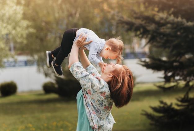 그녀의 머리 위로 그녀의 2 살짜리 유아를 들어 올리는 귀여운 어머니