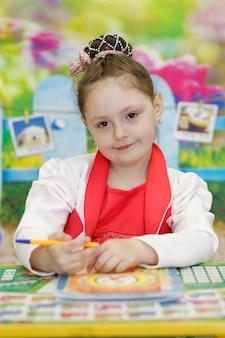귀여운 미취학 아동이 학교 책상에 앉아 펜을 들고 카메라를 보고 있습니다.