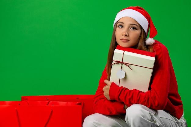 Милая симпатичная девушка в шляпе деда мороза обняла свой праздничный подарок возле зимних торговых сумок и задумалась. .