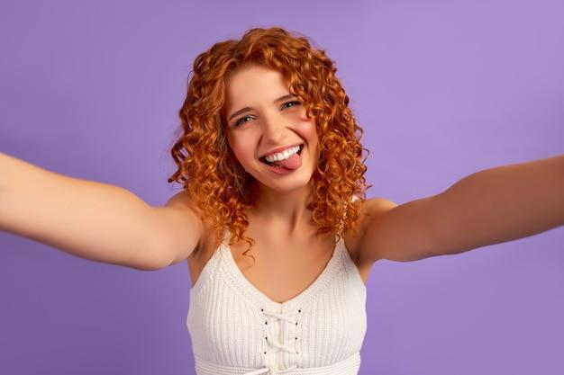 面白いカールを持つかわいい赤毛の女の子は彼女の舌を突き出して、紫色で隔離されたスマートフォンで自分撮りをします