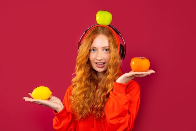 Милая рыжеволосая девушка с длинными вьющимися волосами с веснушками, в наушниках и с фруктами. портрет на красной стене.