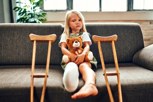 Милая грустная маленькая девочка со сломанной ногой в гипсе сидит на диване, обнимая плюшевого мишку дома. возле дивана есть костыли для быстрой реабилитации.