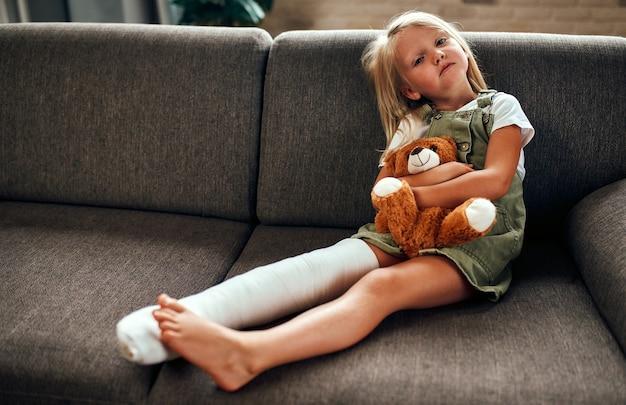 석고 깁스를 하고 다리가 부러진 귀여운 슬픈 소녀가 집 소파에 있는 테디베어를 껴안고 있습니다.