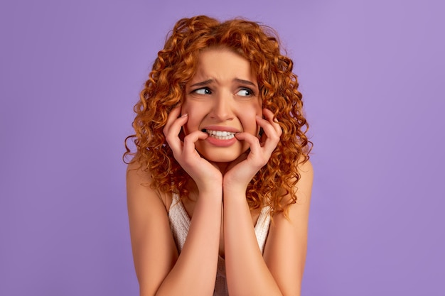 カールしたかわいい怖い赤毛の女の子は彼女の手で彼女の顔を握りしめ、紫色の壁で隔離された側に怯えているように見えます。