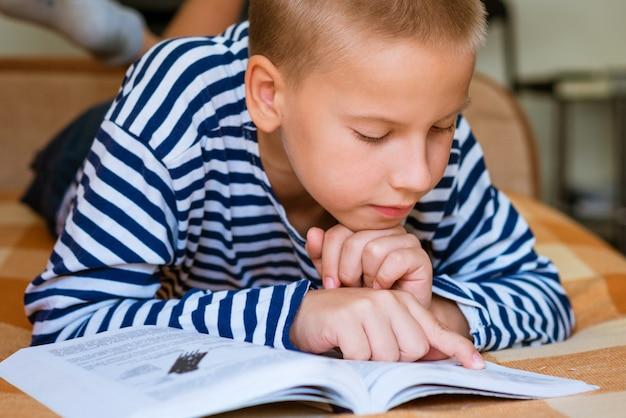 Симпатичный школьник читает книгу, лежа на животе на кушетке, делает уроки по учебе ...