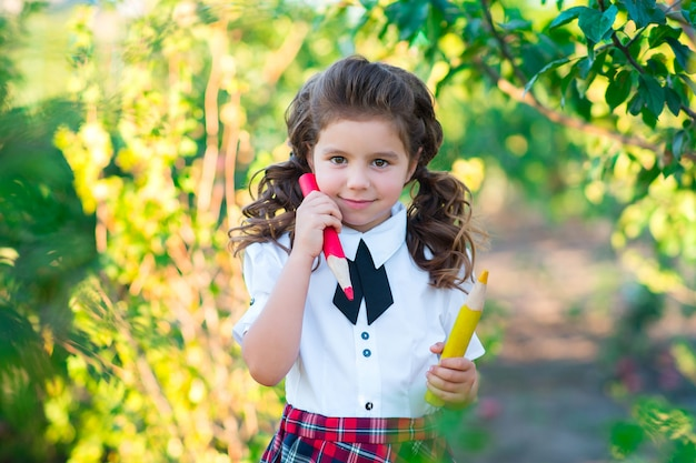 Симпатичная школьница держит в руках карандаши, улыбаясь в камеру. образование. понятие рекламы и людей.