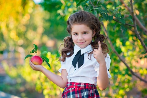 Симпатичная школьница карина держит в руках красное яблоко, улыбаясь в камеру. детство. образование. понятие рекламы и людей.
