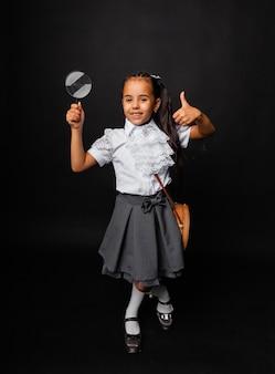 Милая школьница с темными длинными волосами держит увеличительное стекло и показывает класс на темном фоне.