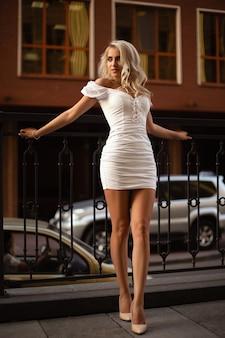 ストリートでポーズをとる美しいカールと魅力的な笑顔のキュートなスレンダーモデル