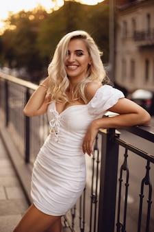 Симпатичная стройная модель с красивыми локонами и очаровательной улыбкой позирует на улице