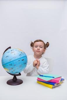 Милый студент сидит за столом с учебниками и глобусом