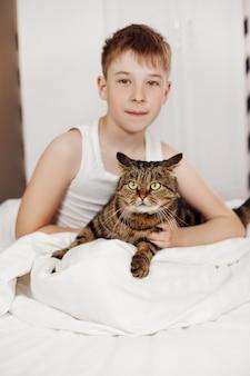 Милый подросток сидит на кровати и держит в руках большого полосатого кота