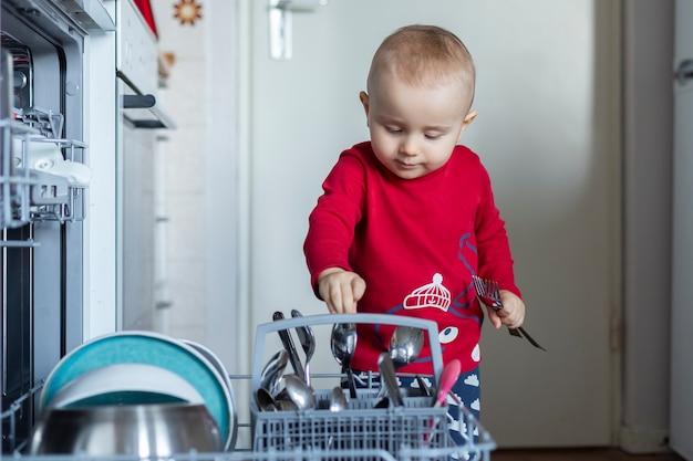 귀여운 유아 소년은 집에서 깨끗한 접시, 숟가락, 식기 세척기 포크를 꺼내는 것을 돕고 있습니다.