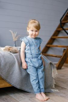 Милая двухлетняя девочка в джинсовом комбинезоне босиком стоит у кровати дома