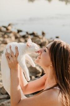 かわいい白い子猫は彼の最愛の愛人の鼻をなめる