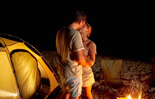 귀여운 여자와 잘 생긴 남자가 밤에는 바다 해변에서 밤에 불 옆 텐트 근처에서 키스하며 낭만적 인 시간을 보내고있다.