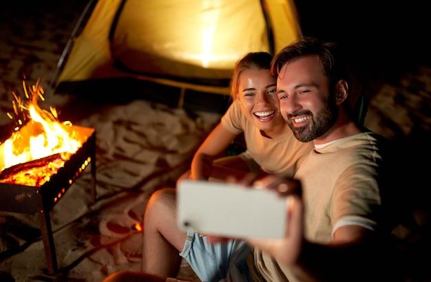 かわいい女性とハンサムな男性が火のそばのテントの近くでロマンチックな時間を過ごし、海沿いのビーチで夜にスマートフォンで自分撮りをします。