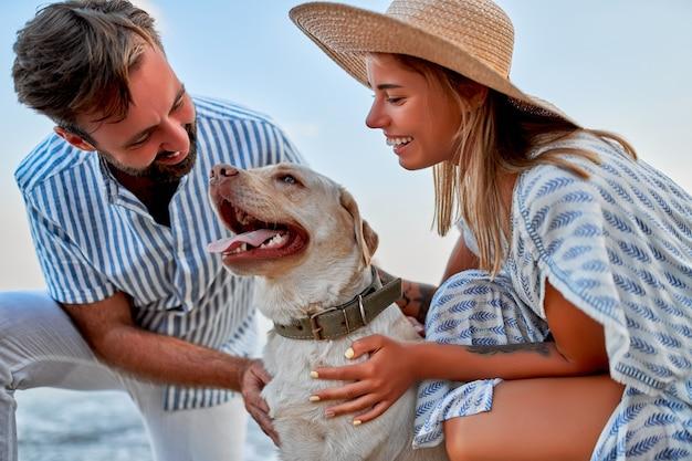Милая женщина в платье и соломенной шляпе и красивый мужчина в полосатой рубашке со своим лабрадором веселятся на берегу моря.