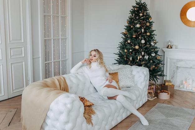 Милая женщина в платье отдыхает сидя на белом диване возле елки в светлом интерьере уютного дома