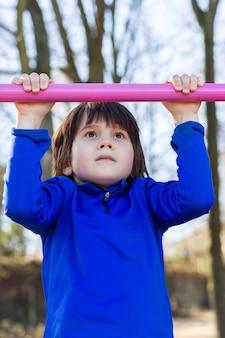 春に路上で懸垂をしているかわいい若い運動少年。スポーツをしているチンアップバーqndの幼児トレーニング。