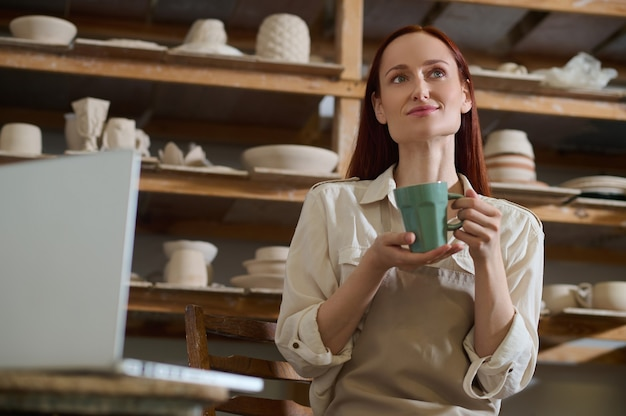 Милая молодая женщина-гончар держит зеленую чашу